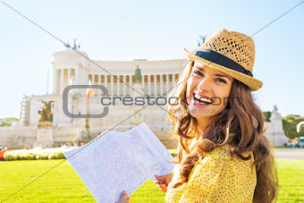 Portrait of happy young woman with map examining attractions on