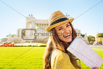 Portrait of smiling young woman with map on piazza venezia in ro