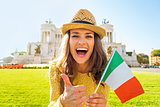 Portrait of happy young woman showing italian flag and thumbs up