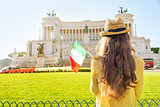 Young woman with italian flag on piazza venezia in rome, italy.