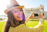 Portrait of happy young woman taking photo on piazza venezia in