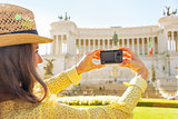Closeup on young woman taking photo on piazza venezia in rome, i