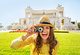 Smiling young woman taking photo on piazza venezia in rome, ital