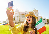 Happy young woman with italian flag making selfie on piazza vene