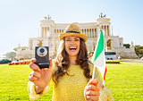 Happy young woman showing italian flag and photo camera while on