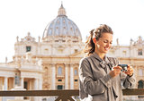 Happy young woman checking photos in camera in front of basilica