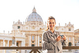 Smiling young woman with photo camera on piazza san pietro in va
