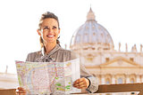Happy young woman with map on piazza san pietro in vatican city