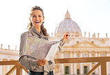 Happy young woman with map pointing on basilica di san pietro in
