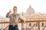 Happy young woman showing thumbs up on piazza san pietro in vati