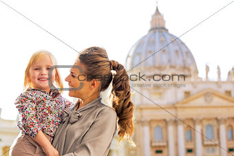 Portrait of happy mother and baby girl in front of basilica di s