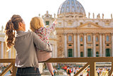 Mother and baby girl pointing on basilica di san pietro in vatic