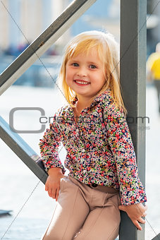 Portrait of happy baby girl sitting on street
