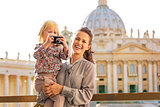 Happy mother and baby girl with photo camera on piazza san pietr