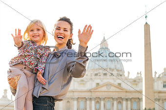 Portrait of happy mother and baby girl waving in front of basili