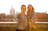 Happy mother and baby girl on street overlooking rooftops of rom