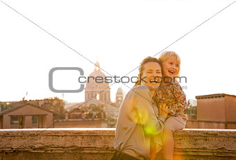 Portrait of smiling mother and baby girl on street overlooking r