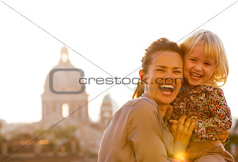 Portrait of happy mother and baby girl against rome panorama on