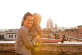 Mother and baby girl on street overlooking rooftops of rome on s