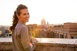 Young woman standing on street overlooking rooftops of rome on s