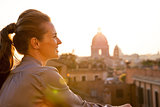 Young woman looking on rome panorama on sunset