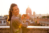 Young woman taking photo of rome panorama on sunset