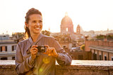 Happy young woman with photo camera on street overlooking roofto