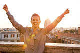 Happy young woman rejoicing on street overlooking rooftops of ro