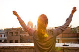 Young woman looking on rome panorama on sunset and rejoicing. re