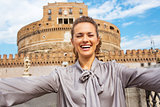 Happy young woman making selfie in front of castel sant'angelo i