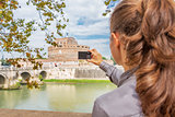 Young woman taking photo of castel sant'angelo in rome italy. re