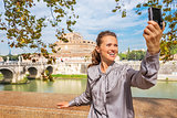 Smiling young woman making selfie on embankment near castel sant