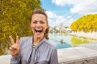 Portrait of happy young woman showing victory gesture while stan