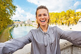 Smiling young woman making selfie on bridge ponte umberto I with