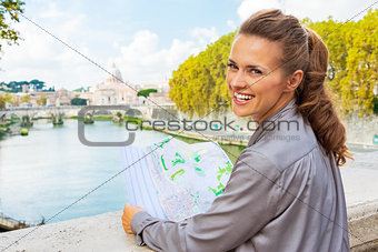 Portrait of smiling young woman with map on bridge ponte umberto