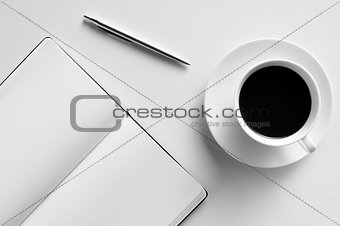 blank notepad, pen and cup of coffee on a white table