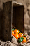 Oranges on stalk in rustic kitchen setting with old wooden box