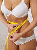Sexy woman measuring her slim waist