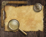vintage nautical compass and loupe on table with treasure map