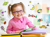 Happy child in glasses reading book. Early education in kindergarten concept.