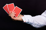 man's hand holding three cards and the ace in the hole