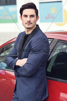 Attractive young businessman standing near a red car.