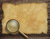 old treasure map on wooden desk with magnifying glass