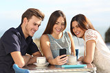 Group of friends watching social media in a smart phone