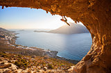 Male rock climber flexing his bicep while hanging on one arm at sunset. Climbing along roof in cave, Kalymnos, Greece