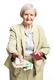 Senior woman giving money and holding passport, hand with money in focus. Isolated over white