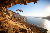 Female rock climber hanging on rope after unsuccessful attempt to take next handhold on cliff while lead climbin