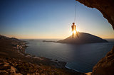 Rock climber hanging on rope while lead climbing at sunset, with Telendos island in background. Kalymnos island, Greece.