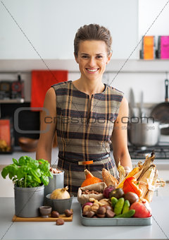 Portrait of happy young housewife with vegetables in kitchen