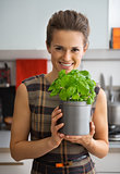 Portrait of happy young housewife with fresh basil